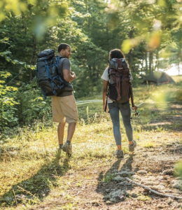 Couple backpacking through woodlands