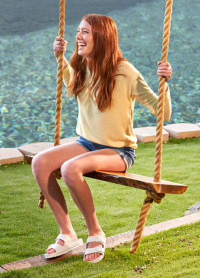 Young red-headed girl on a swing in yellow tshirt and denim shorts wearing light brights sandals