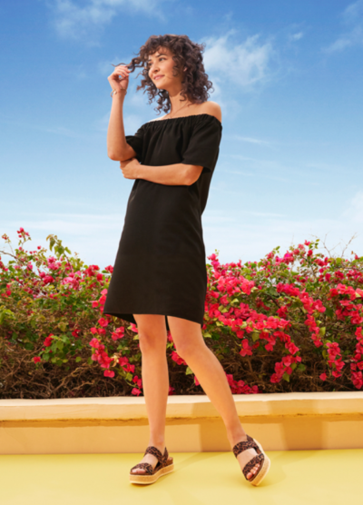 Young woman in black dress wearing platform sandals