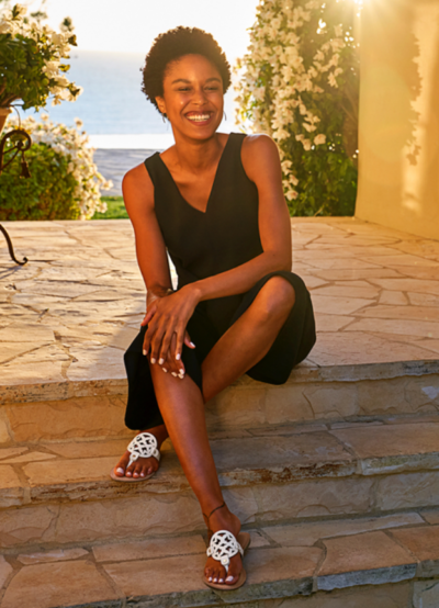 Young black woman in black dress wearing white sandals